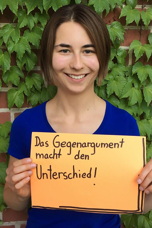"""Eine junge Frau mit blauem T-Shirt hält ein orangenes Blatt vor sich in den Händen. Die Aufschrift lautet: """"Das Gegenargument macht den Unterschied!"""" © Servicestelle Jugendbeteiligung e. V."""
