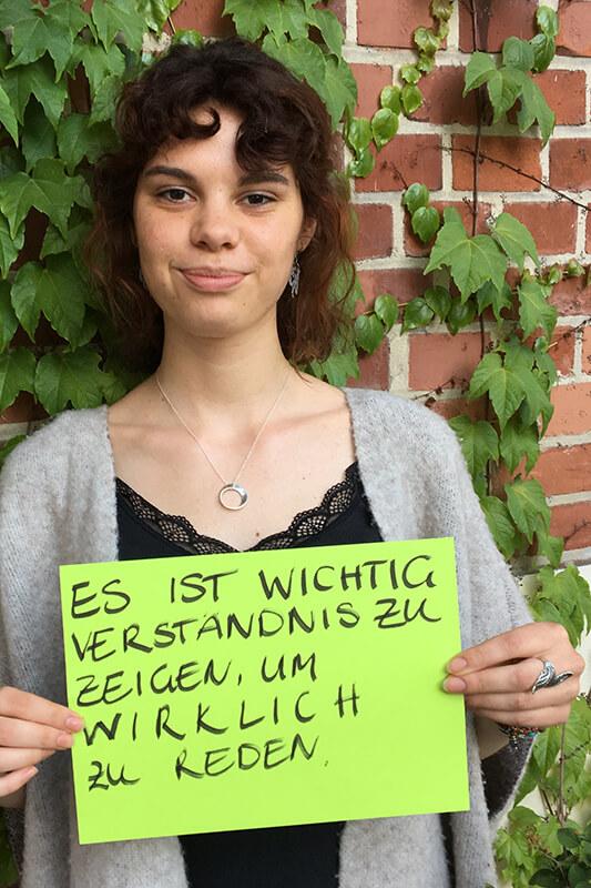 """Eine junge Frau hält ein grünes Blatt vor sich in den Händen. Die Aufschrift lautet: """"Es ist wichtig Verständnis zu zeigen, um wirklich zu reden."""" © Servicestelle Jugendbeteiligung e. V."""