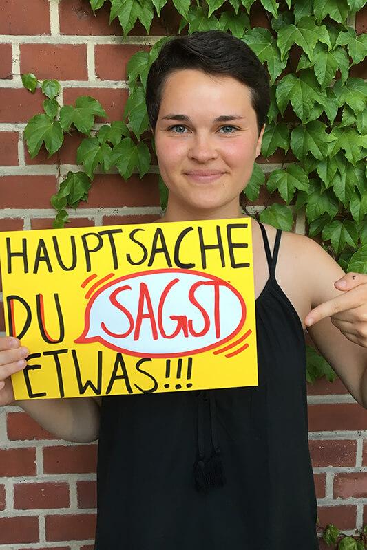 """Eine junge Frau hält ein gelbes Blatt vor sich in den Händen. Die Aufschrift lautet: """"Hauptsache du sagst etwas!!!"""". © Servicestelle Jugendbeteiligung e. V."""
