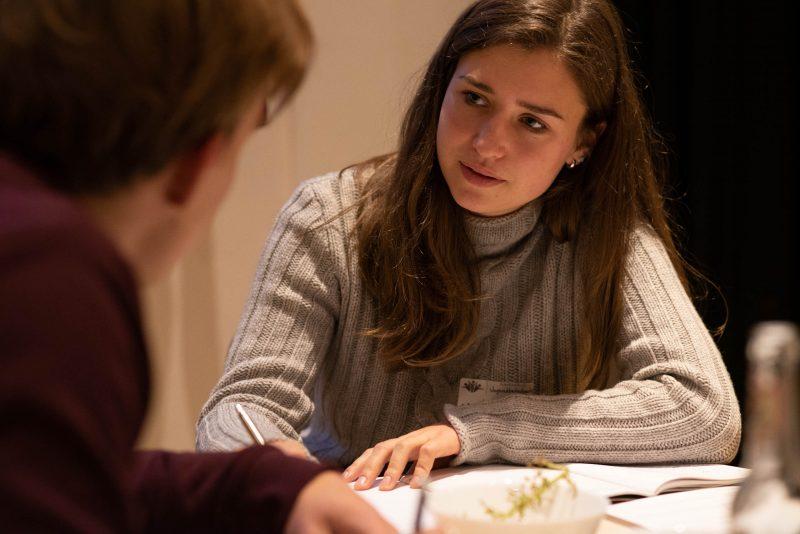 Im Fokus sitzt eine junge Frau mit grauem Pullover an einem Tisch und schreibt etwas auf. Eine weitere Person sitzt rechts von ihr. © Servicestelle Jugendbeteiligung e. V.