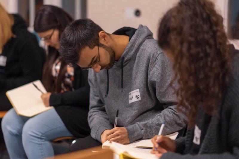 Im Fokus des Bildes sitz ein junger Mann, der etwas in ein Notizbuch schreibt. Um ihn herum sitzen weitere junge Menschen die ebenfalls etwas in Notizbücher schreiben.